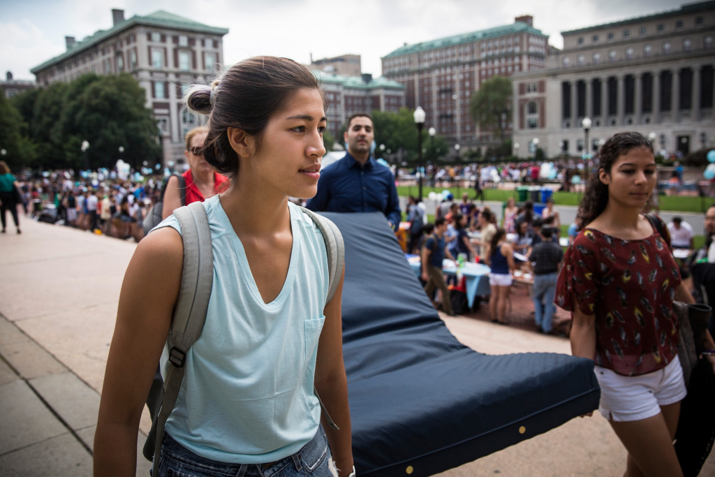 NEW YORK, NY - SEPTEMBER 05:  Emma Sulkowicz (L),  a senior visual arts student at Columbia University, carries a mattress, with the help of three strangers who met her moments before, in protest of the university's lack of action after she reported being raped during her sophomore year on September 5, 2014 in New York City.  Sulkowicz has said she is committed to carrying the mattress everywhere she goes until the university expels the rapist or he leaves. The protest is also doubling as her senior thesis project.  (Photo by Andrew Burton/Getty Images)