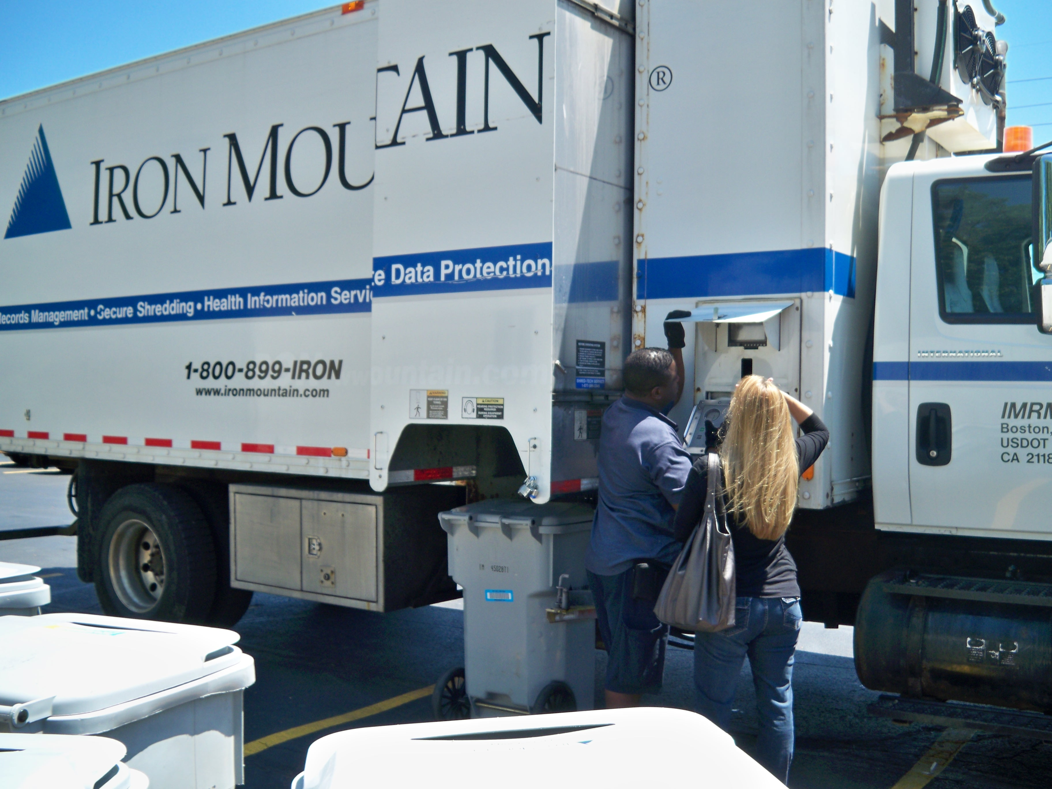 A participant witnessing her documents being shredded via the camera on the mobile shred truck.
